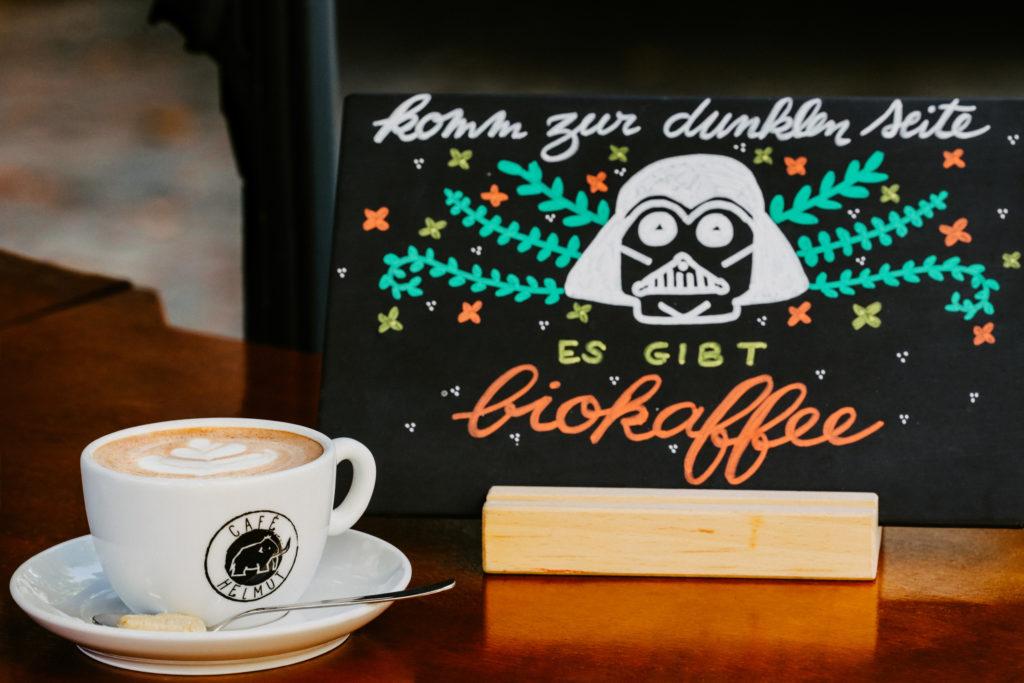 """Tasse Kaffe (mit Helmut Logo) mit einem Schild """"komm zur dunklen seite es gibt biokaffee"""""""